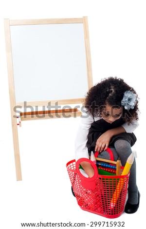 Little girl taking something from her basket bag - stock photo