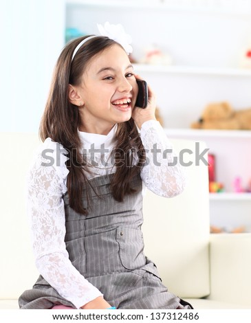 Little girl talking on the phone. - stock photo