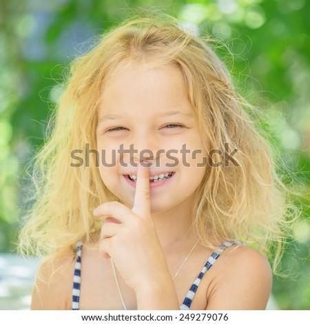 Little girl talking presses finger to his lips against green of Park in summer. - stock photo