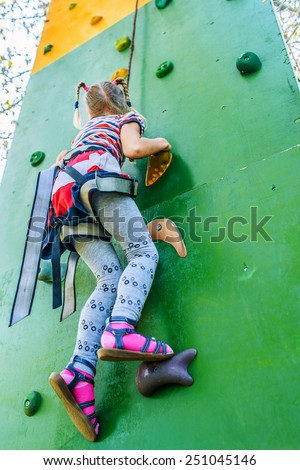 Little girl talking trains on climbing wall in summer city park. - stock photo