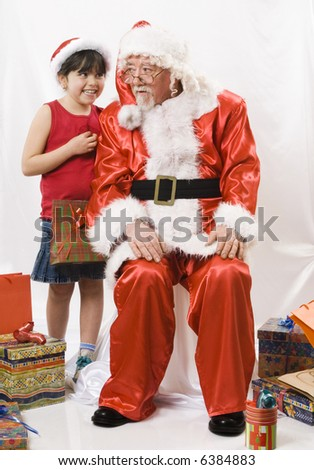 little girl talking with an old santa claus - stock photo