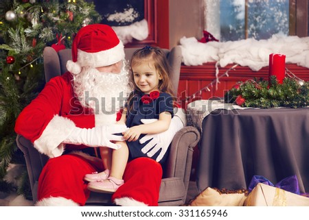 Little girl telling her Christmas wish in Santa Claus near the Christmas Tree - stock photo