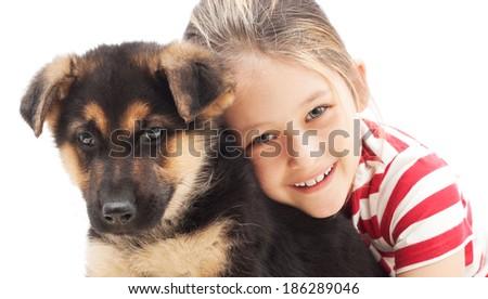 little girl tenderly embraces a German Shepherd puppy - stock photo