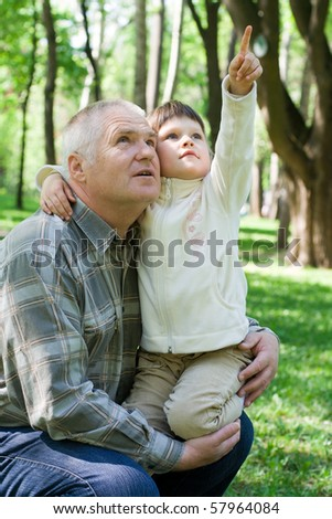 Little girl tenderly embraces grandfather in the park, sits on his arms and points up. Both look up - stock photo