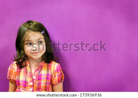 Little girl thinking on purple wall - stock photo