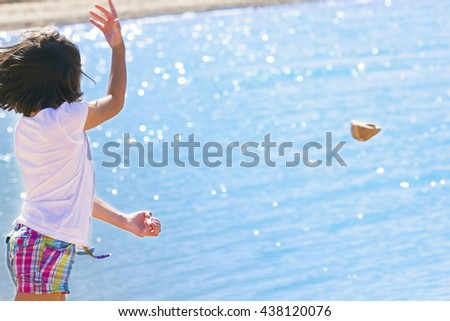 Little girl throws rocks into the water. Sea in background. Copy space. - stock photo