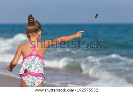 Little girl throws rocks into the water. Sea in background. Copy space in bright blue sky - stock photo