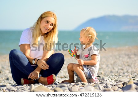 little girl toddler on the beach autumn summer spring lollipop colors jeans 2 years old with mom mum