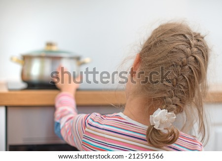 Little girl touches hot pan on the stove. Dangerous situation at home.