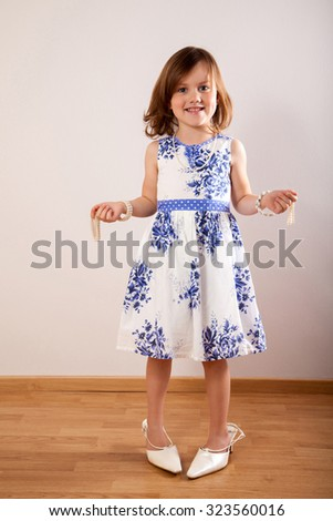 Little girl tries on a mum's beads and in her mother's shoes - stock photo