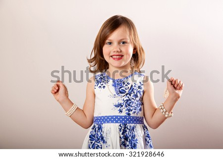Little girl trying on her mother's jewelery - stock photo