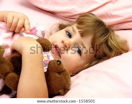 Little girl tucked in bed with her teddybear - stock photo