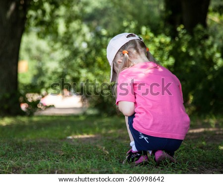 Little girl turning back and  gathering something in grass - stock photo