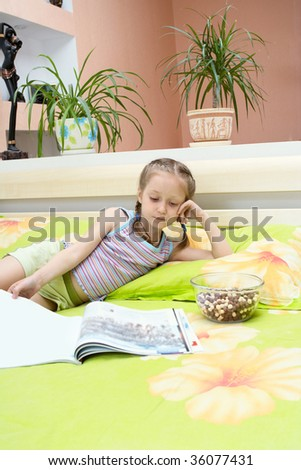 little girl turning over the pages of magazines sitting on the parents` bed