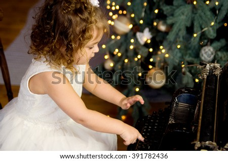 Little girl typing on a typewriter