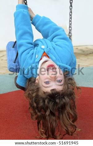 little girl upside down on park playground swing - stock photo