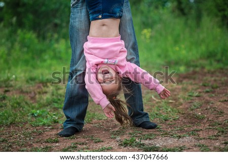 Little girl upside down  outdoors in summer - stock photo