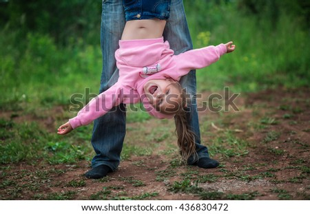 Little girl upside down upside down outdoors in summer - stock photo