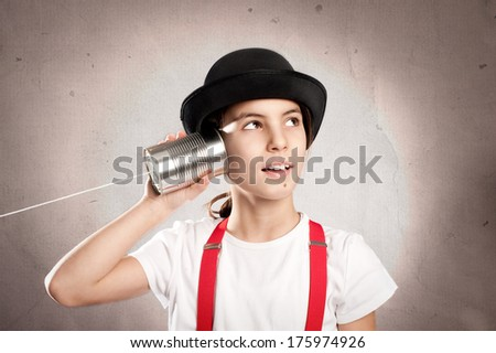 little girl using a can as telephone on a gray background - stock photo