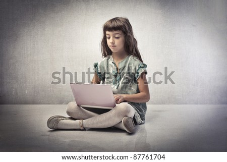 Little girl using a laptop - stock photo