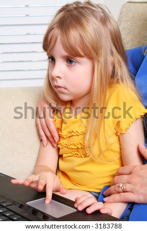 Little girl using a laptop with mother close behind helping