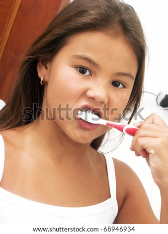 Little girl using a toothbrush. - stock photo