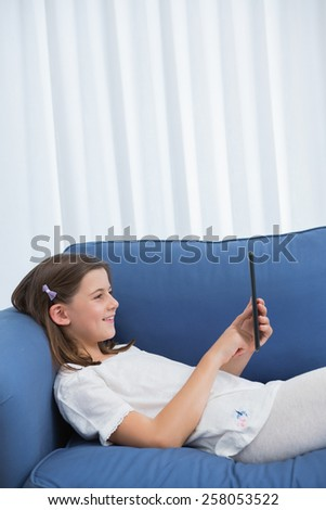 Little girl using digital tablet on the couch at home in the living room - stock photo