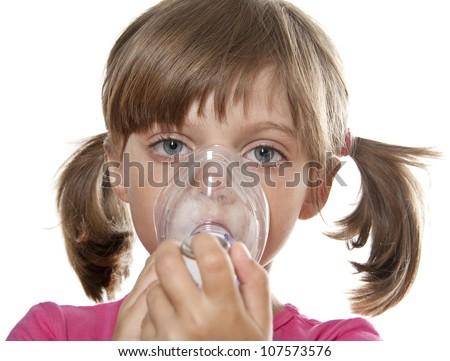 little girl using inhaler - respiratory problems - stock photo