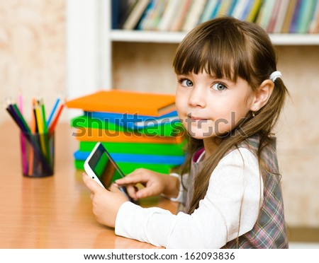 little girl using tablet computer. looking at camera - stock photo