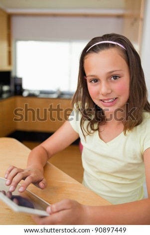 Little girl using tablet in the kitchen - stock photo