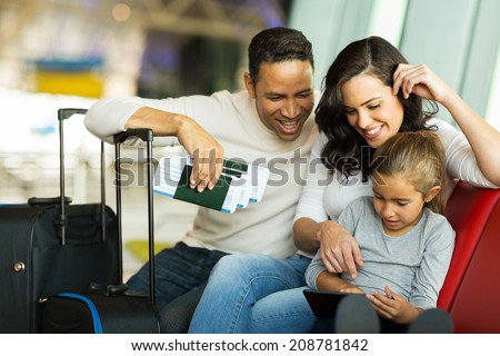 little girl using tablet pc with parents at airport while waiting for their flight - stock photo