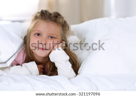 Little girl wake up early morning after sleeping and lying in her bed. Smiling blonde female child awakening portrait in bedroom. Sweet dreams and good morning concept