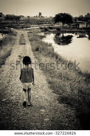 Little girl walk in the country, dark tone - stock photo