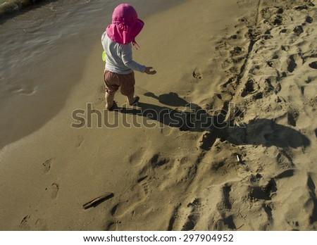 little girl walking at beach - stock photo