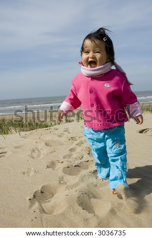 little girl walking at the beach - stock photo