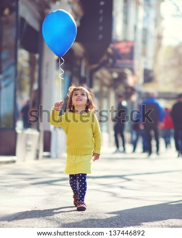 Little Girl walking down the street with a blue balloon - stock photo