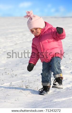 Little girl walking in a snowy landscape. - stock photo