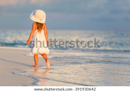 Little girl walking on beautiful ocean beach - stock photo