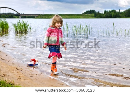 little girl, walking on river, pulls a ship for a string