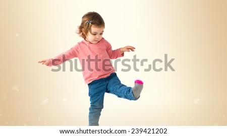 Little girl walking over ocher background - stock photo