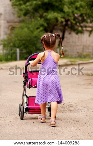 Little girl walking with a toy stroller. Little Mama. - stock photo
