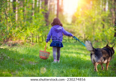 Little girl walking with dog in the forest - stock photo
