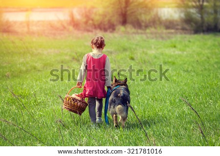Little girl walking with dog on the meadow  back to camera - stock photo