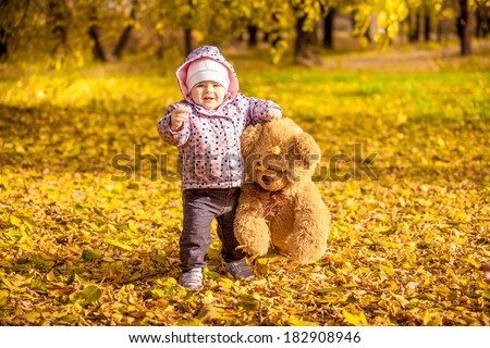Little girl walking with teddy bear at autumn park