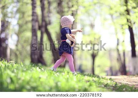 little girl walks in the park in summer - stock photo