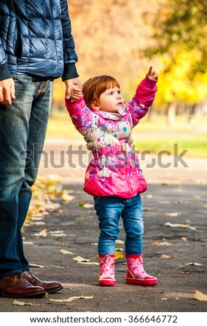 Little girl walks with my dad, pointing to something in the park - stock photo