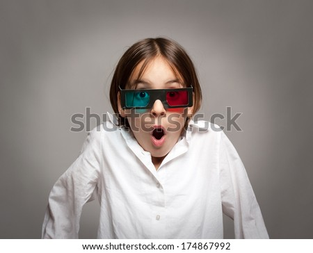 little girl watching a a movie wearing 3d glasses
