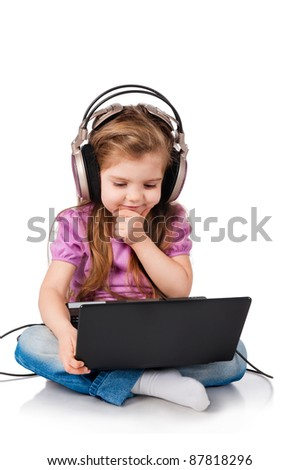 little girl watching on headphones in a laptop - stock photo