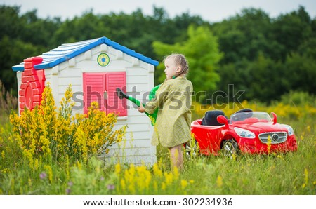 little girl watering flowers in front of his house - stock photo