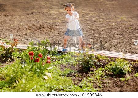 Little girl watering flowers in the garden - stock photo